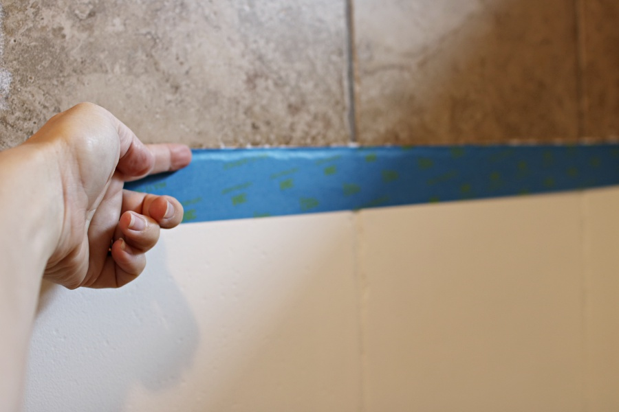 Re tape the decorative area, this time overlapping the paint onto the white painted tile.  This will create a sharp line.