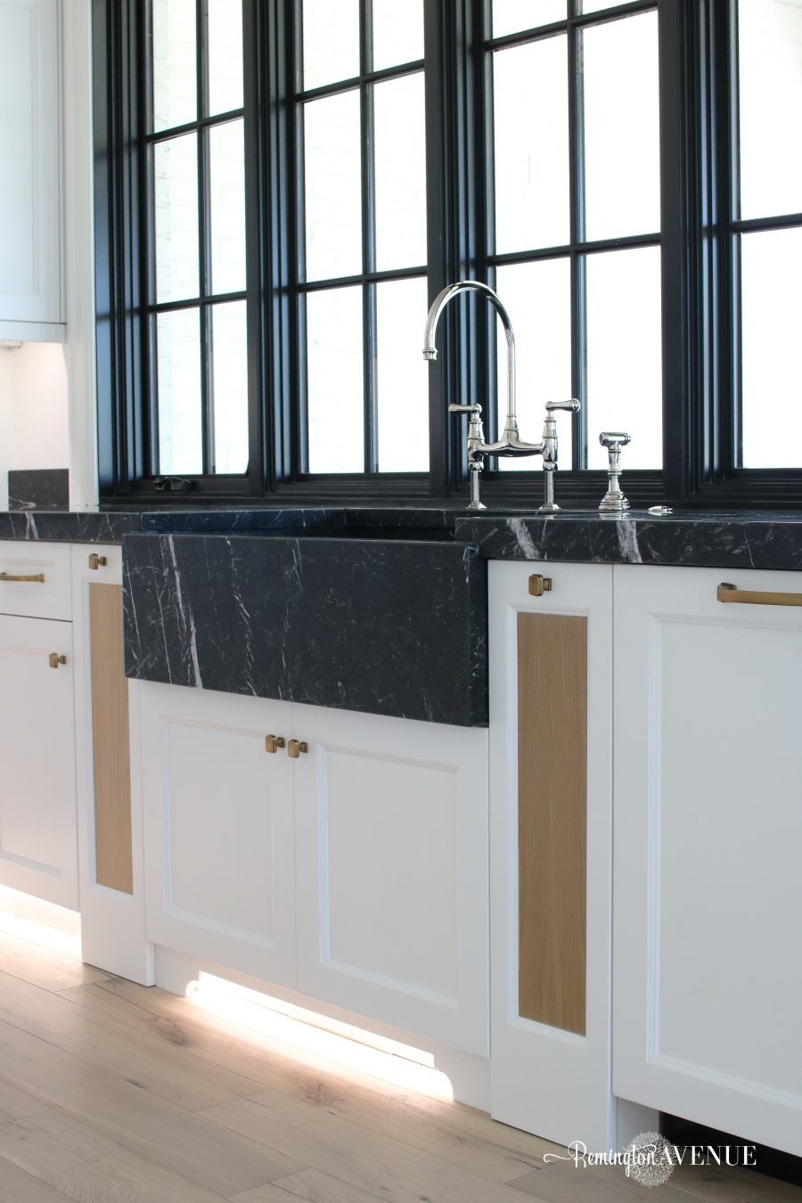 French Country Modern Kitchen with Black Marble Counters and marble farmhouse sink