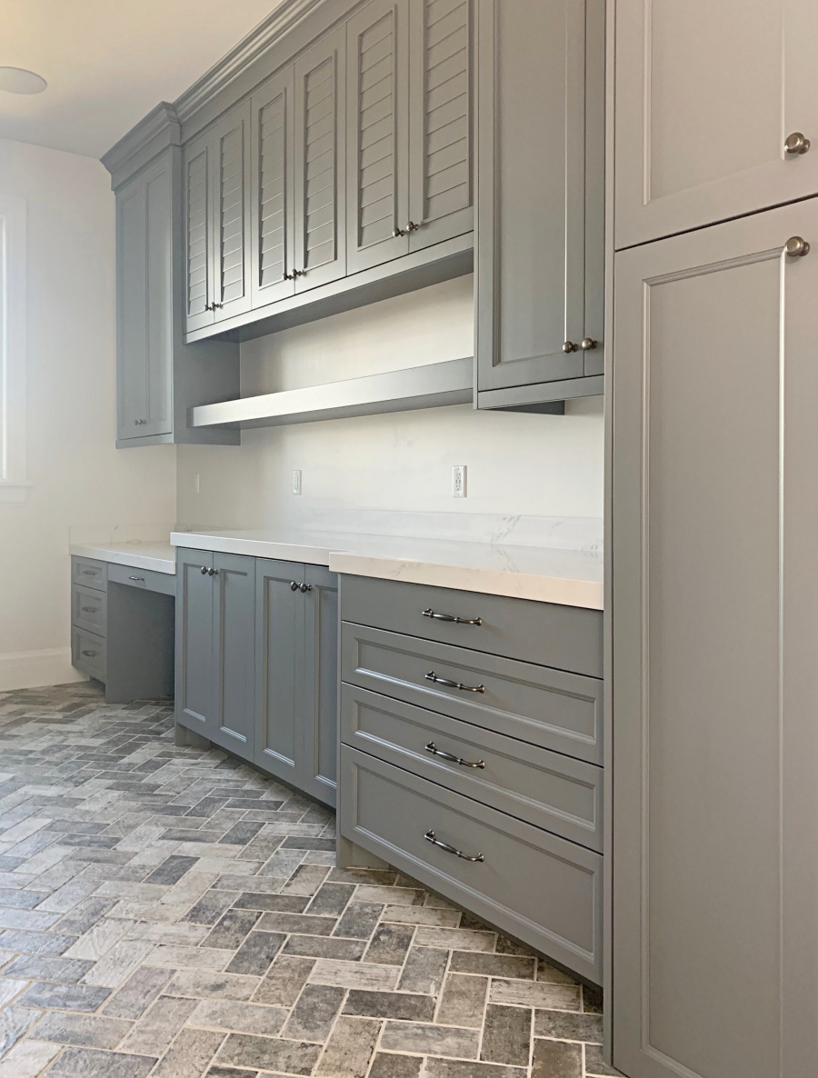elegant laundry:mudroom with herringbone brick floor
