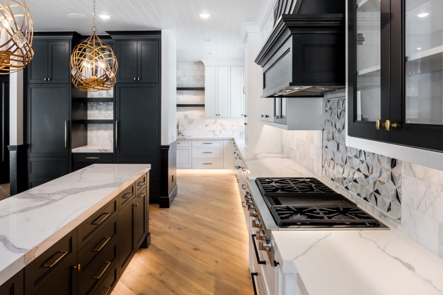 glam kitchen with marble backsplash and black & white cabinets