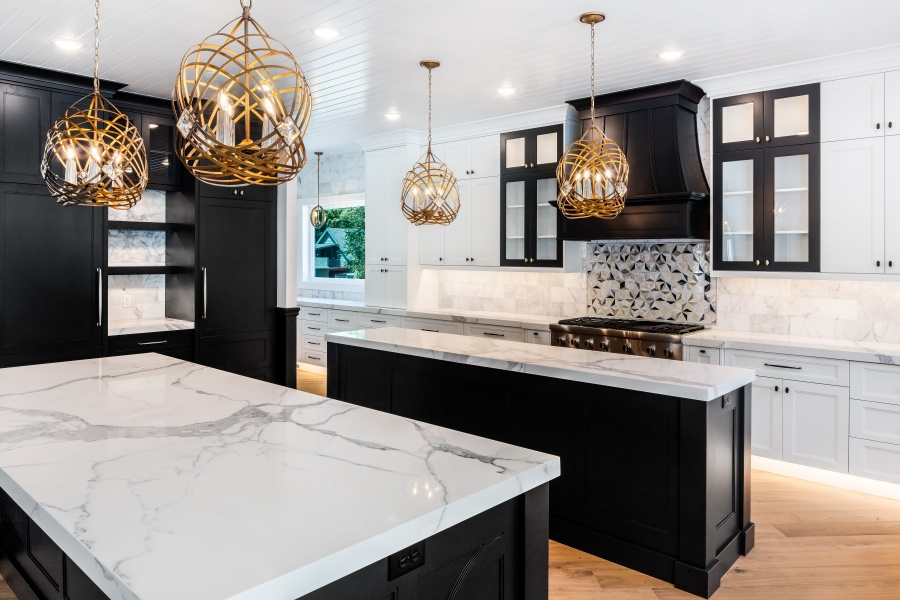 black and white glam kitchen with brass lighting and marble backsplash