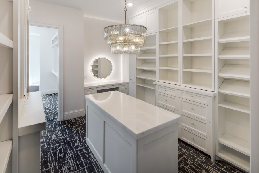 glam master closet with makeup vanity and chandelier